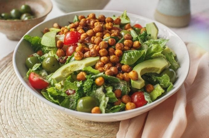 Large white bowl of fresh Caesar salad made with all vegan ingredients, on a woven placemat on the bench