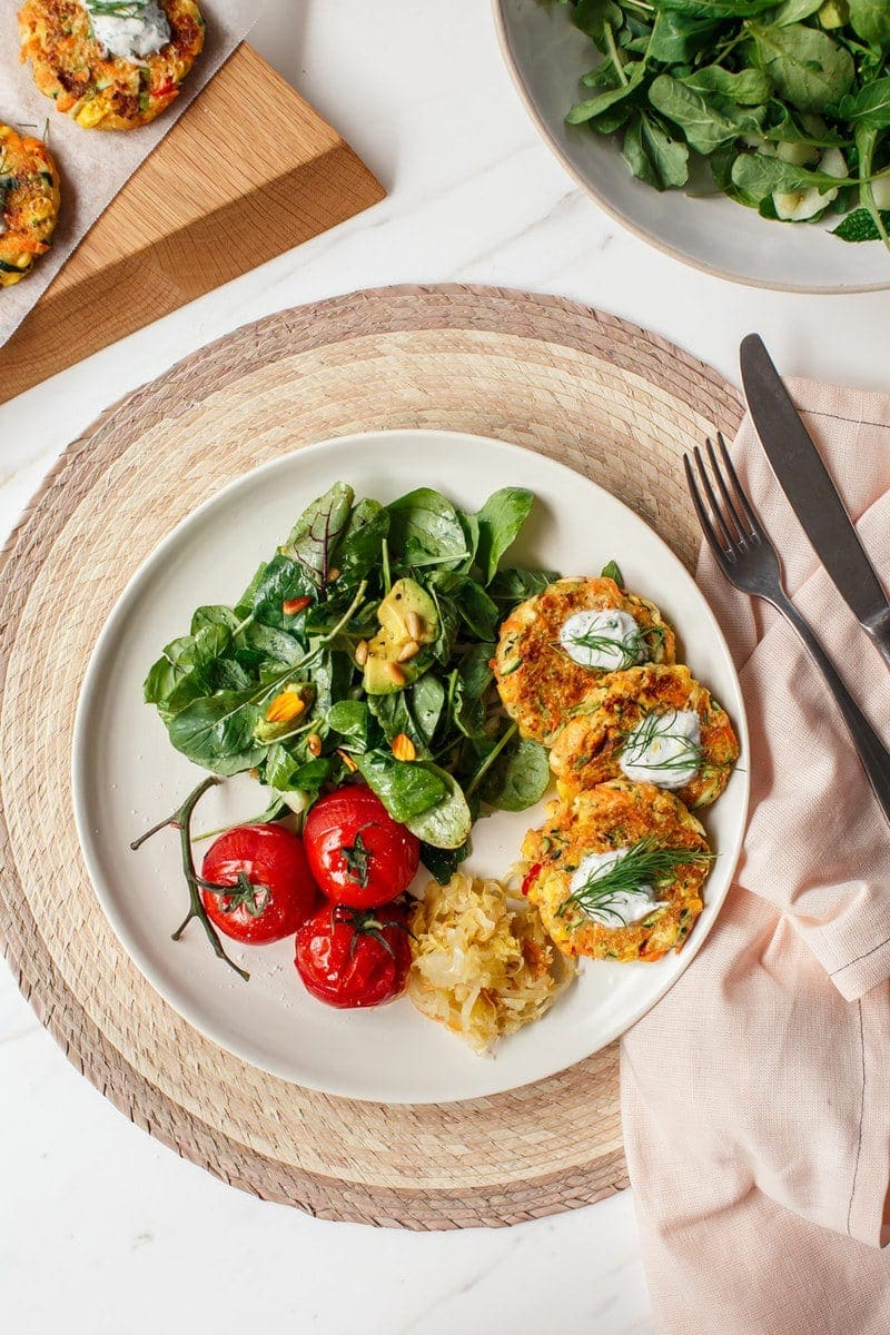 A nutritionally balanced dinner plate filled with fresh salad, roasted tomatoes, sauerkraut and bite-sized vegetable fritters
