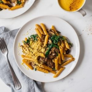 Creamy mushroom pasta on a plate with a blue napkin