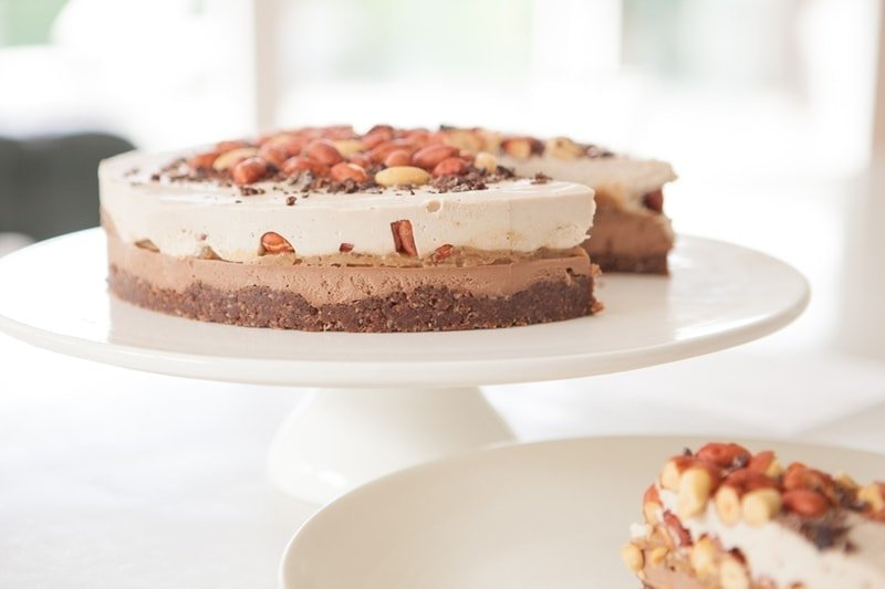 Raw Snickers Cake on a white cake stand cut and served onto side plates