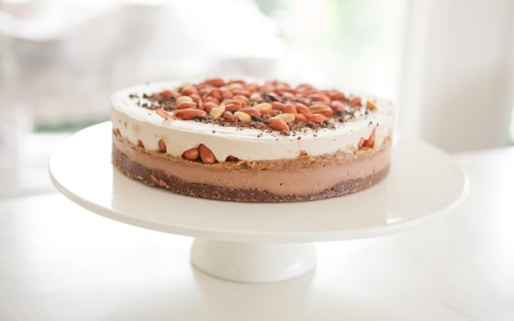 No-bake Snickers Cake on a white cake stand by the kitchen window