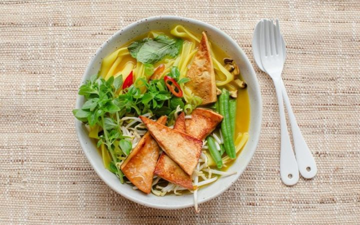 Close up of a bowl of pho made with vegan ingredients, on a woven placemat