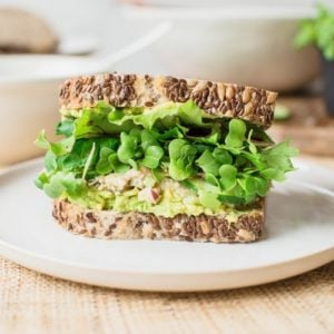 Close up of a large chickpea salad sandwich on a plate