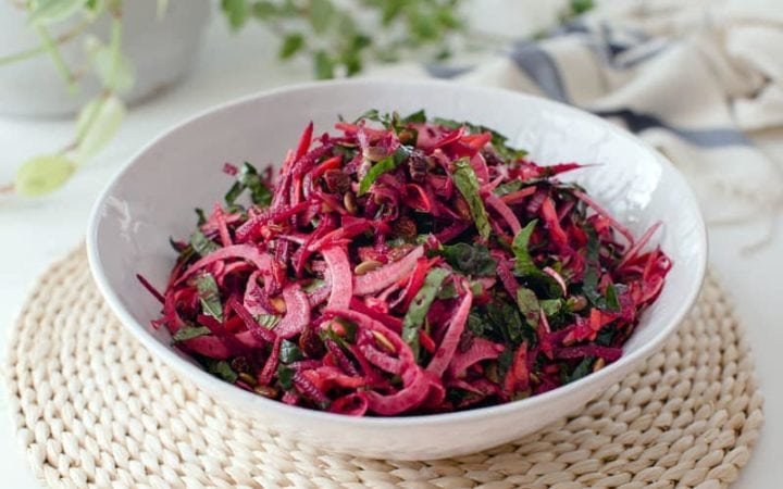 Close up of a bowl of colourful raw beet salad in a white bowl on a woven placemat