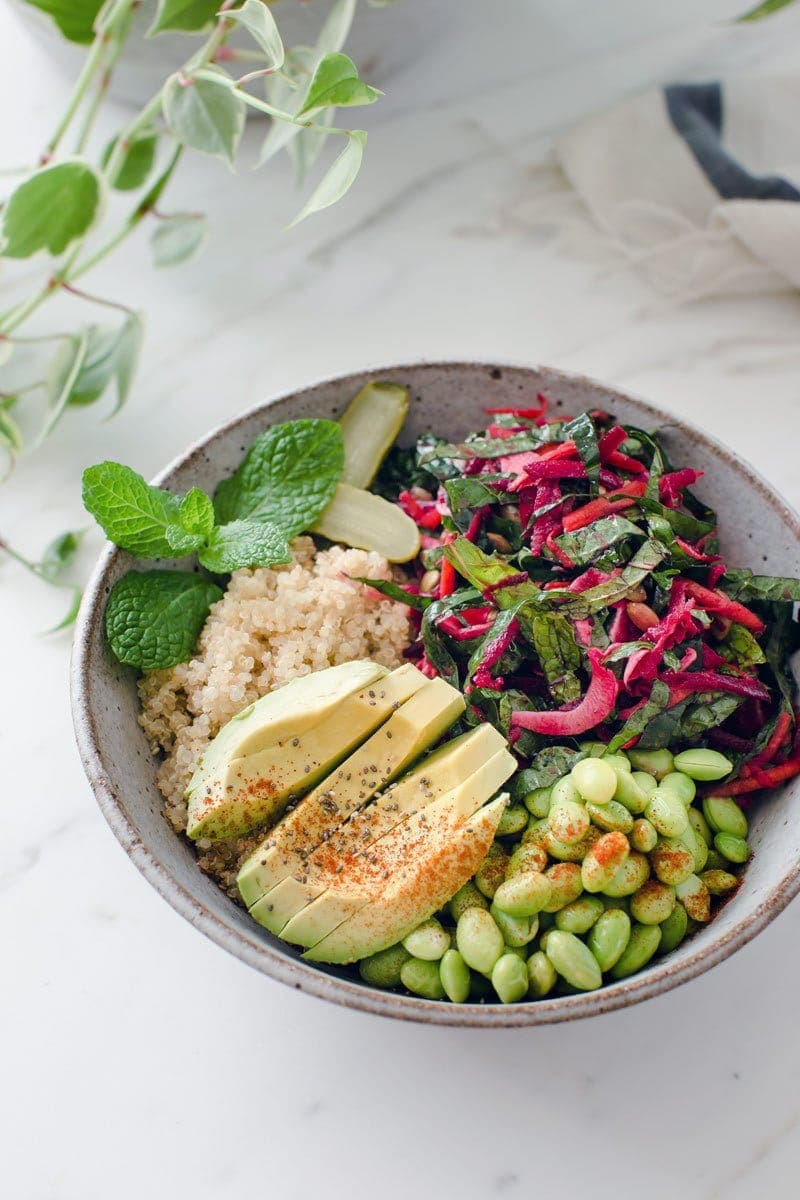 A Buddha bowl containing fresh raw beetroot salad, quinoa, edamame beans and avocado