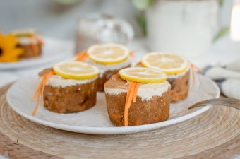 A plate of four individual raw carrot cake muffins topped with lemon cashew frosting on a woven placement