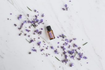 doTERRA lavender essential oil surrounded by strewn lavender flowers on a marble surface