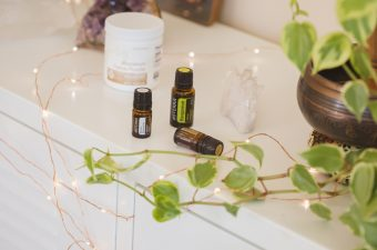 Three essential oils - bergamot, roman chamomile and sandalwood, on a white cabinet with fairy lights