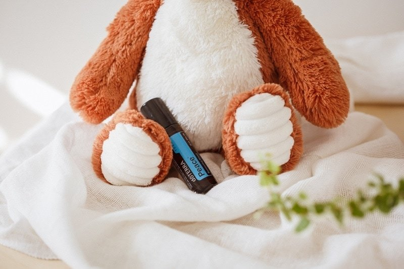Peace essential oil nestled in beside a soft toy