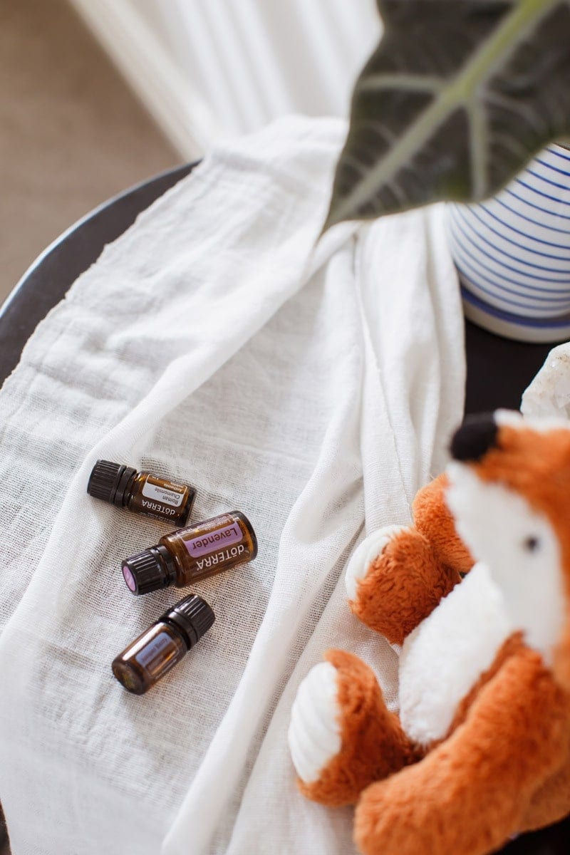 Lavender, Chamomile and Juniper Berry Essential Oils for Kid's Sleep, on a beside table