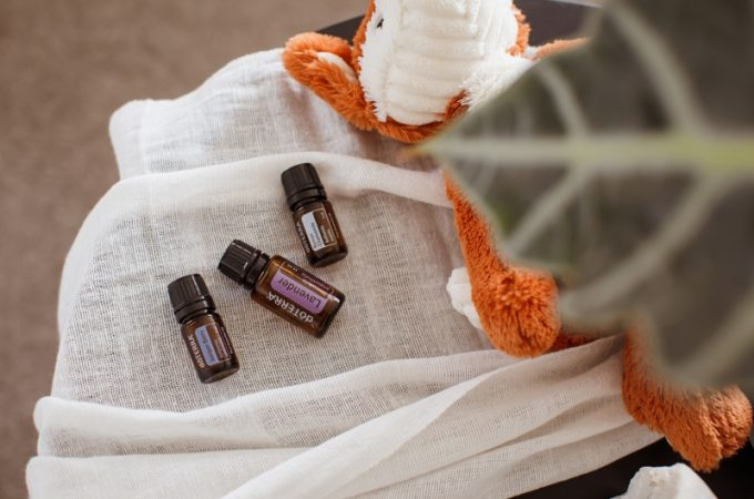 Essential oils for kids sleep on a bedside table next to soft toy