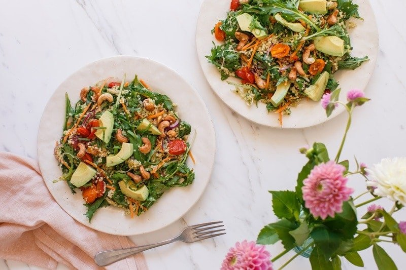 Two plates filled with a quinoa salad with avocado and quick pickles