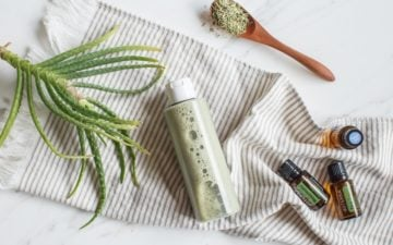 Bottle of homemade shampoo with herbs, aloe and essential oils on a towel