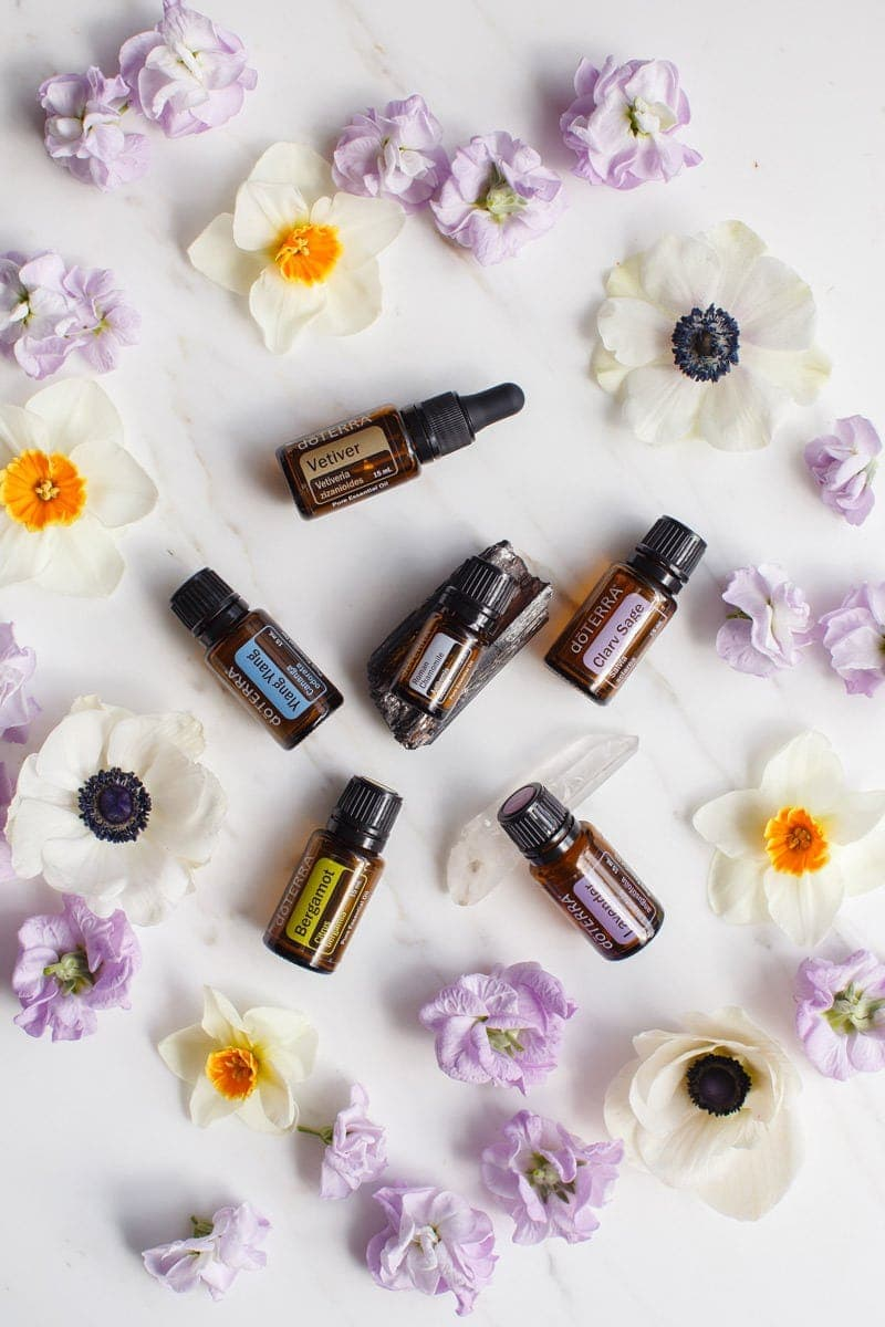 6 essential oils for stress on a marble surface surrounded by colourful flowers
