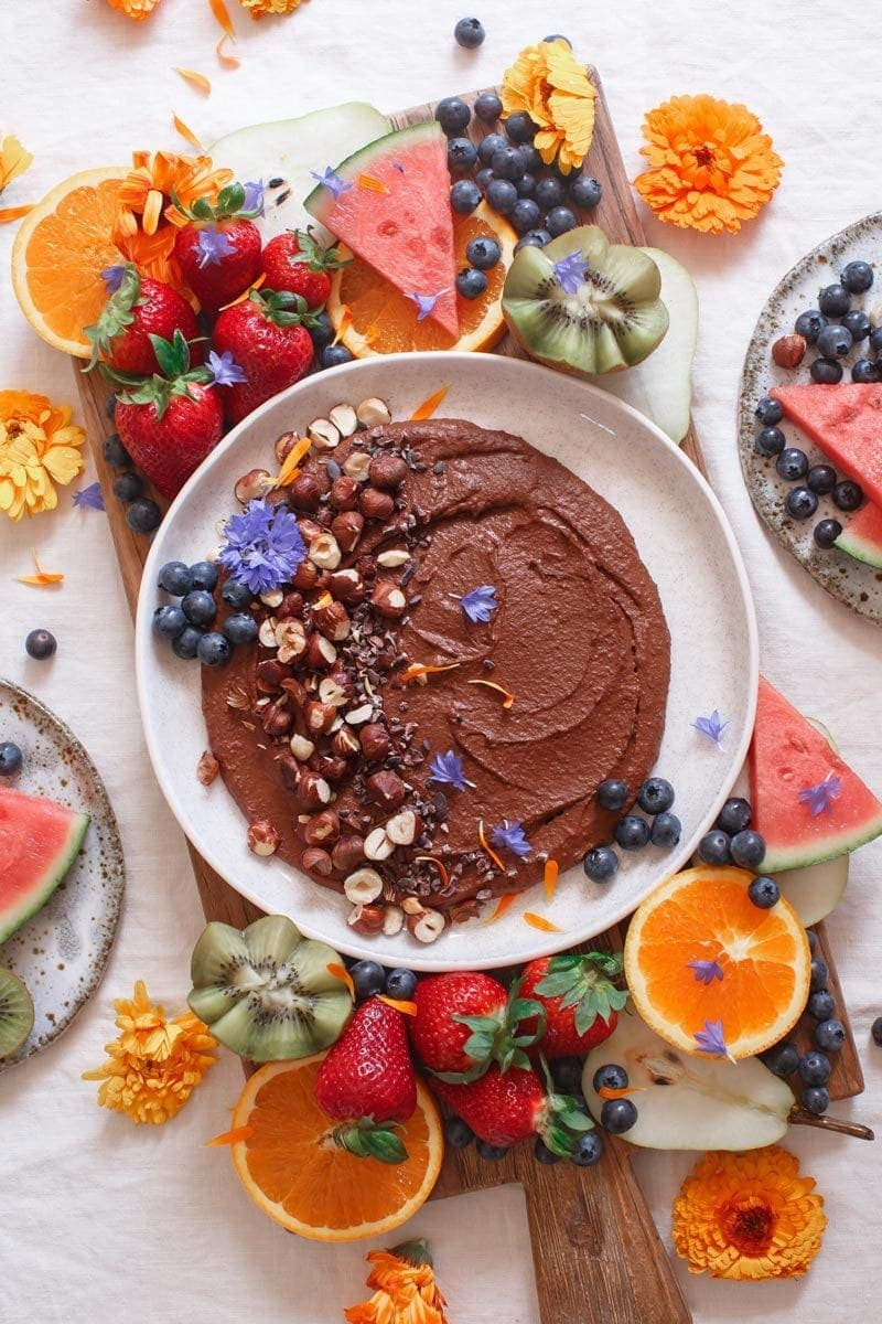 Chocolate hummus decorated with flower petals and chopped nuts on a platter filled with beautifully cut fresh fruits
