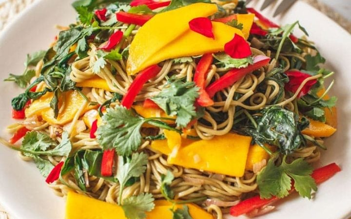 Mango Soba Noodle Salad on a woven placement with serving spoon
