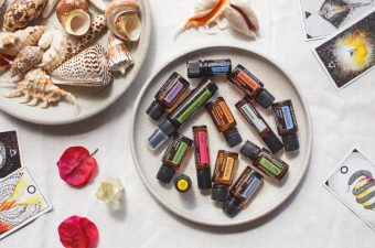 A selection of summer essential oils on a platter next to some shells