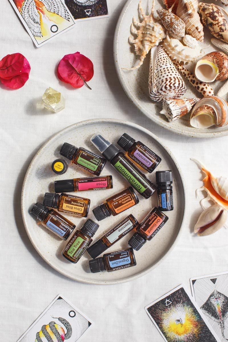 Hero shot of top summer essential oils surrounded by sea shells and flowers