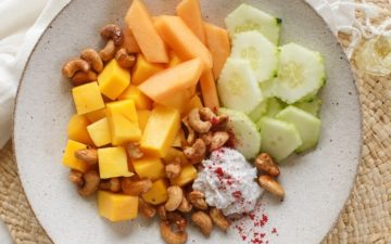 Maple roasted cashews scattered over a bowl of fresh fruit