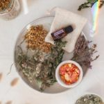 Ceramic plate filled with dried herbs, flower petals and a bottle of clary sage oil, all are ingredients needed to make a herbal bath
