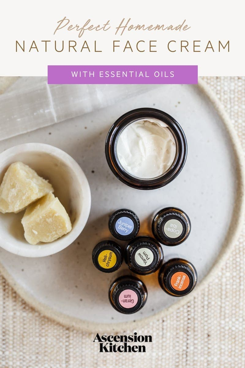 Close up of an open jar of face cream surrounded by various essential oils on a plate, the recipe title is written across the top of the image