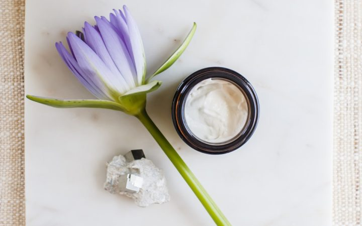 A jar of pure white skin cream styled beautifully with a flower beside it