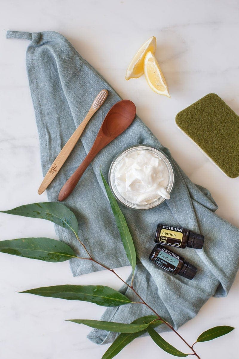 Flat lay of a jar of soft scrub with a few essential oils, a sprig of eucalyptus and a wooden spoon