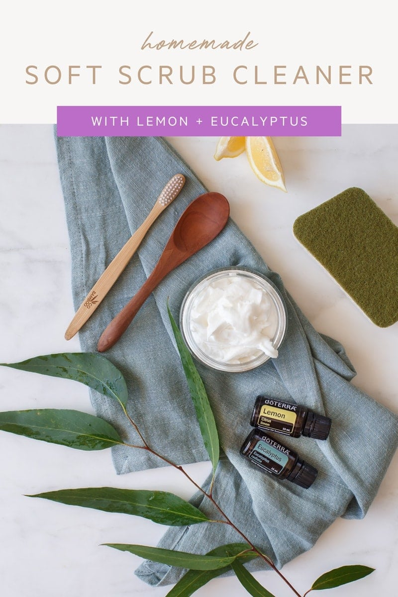 Flat lay of a kitchen bench top with a jar of soft scrub, essential oils and cleaning sponge