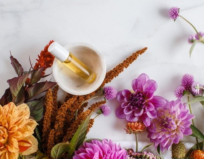 Home made perfume blend surrounded by flowers