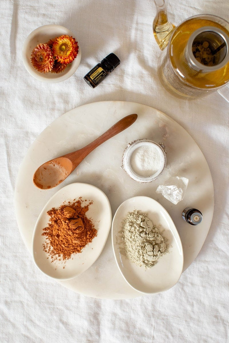 Flat lay of ingredients used to make a homemade face mask for acne, on a white marble surface.