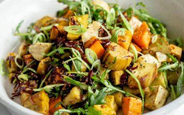 Close up of tri colour roasted kumara salad in a ceramic serving bowl