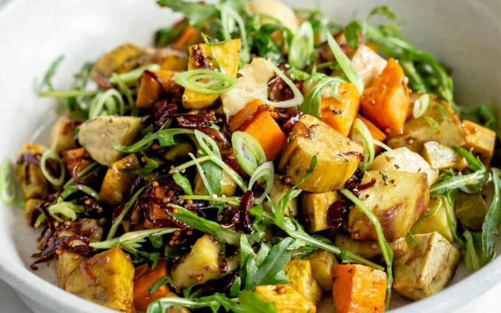 Close up of tri colour roasted kumara salad in a ceramic serving bowl