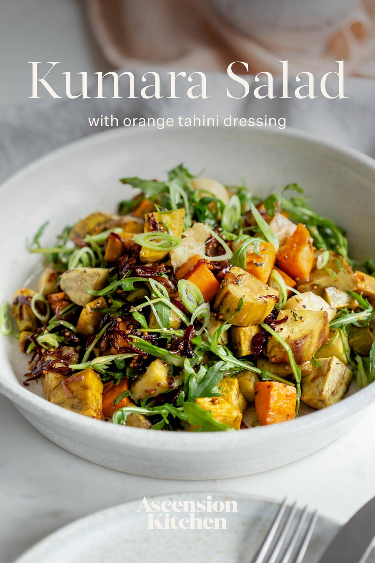 Large bowl of roasted kumara salad topped with spring onions, with the recipe title written over the top