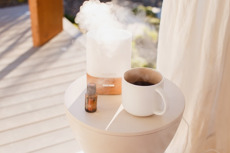 A mug of coffee next to a diffuser puffing out steam, and a bottle of doTERRA Frankincense