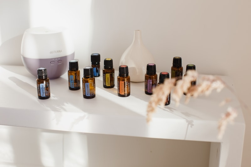The ten oils from doTERRA's Home Essentials Kit on a white bench with soft light and shadows
