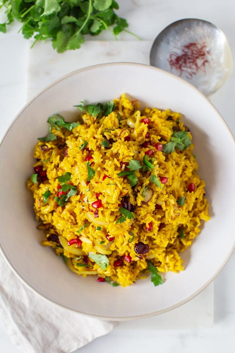 The finished saffron rice recipe, topped with fresh coriander, on a marble board