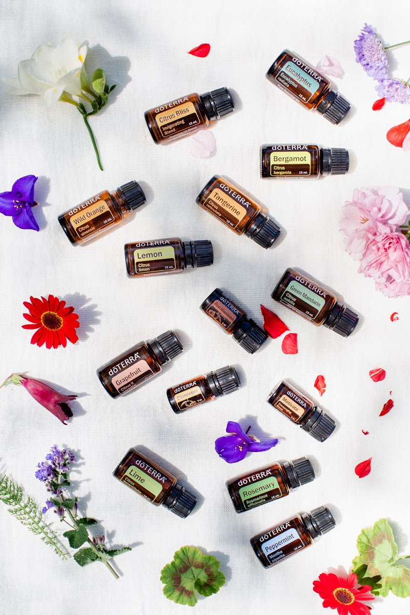 Detail of bottles of essential oils for energy surrounded by flowers in dappled light