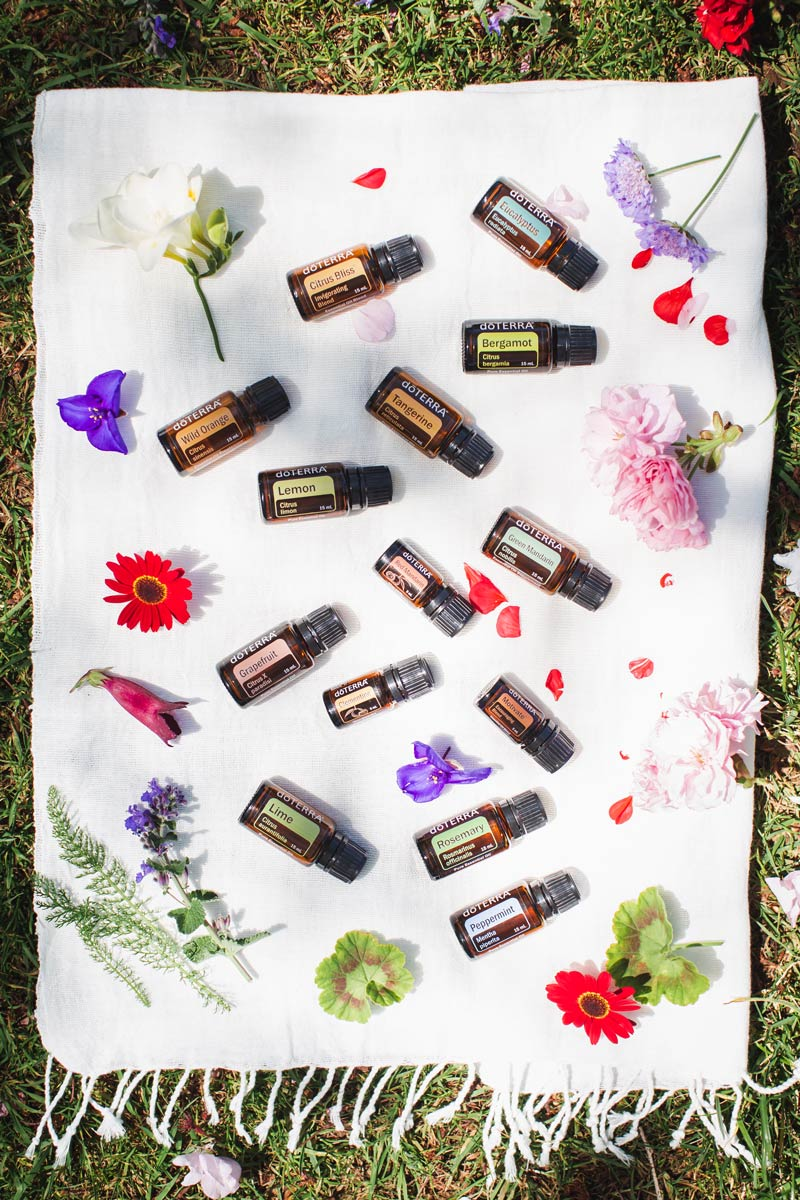 Essential oils for Energy laid out on a cotton towel, surrounded with flowers and petals