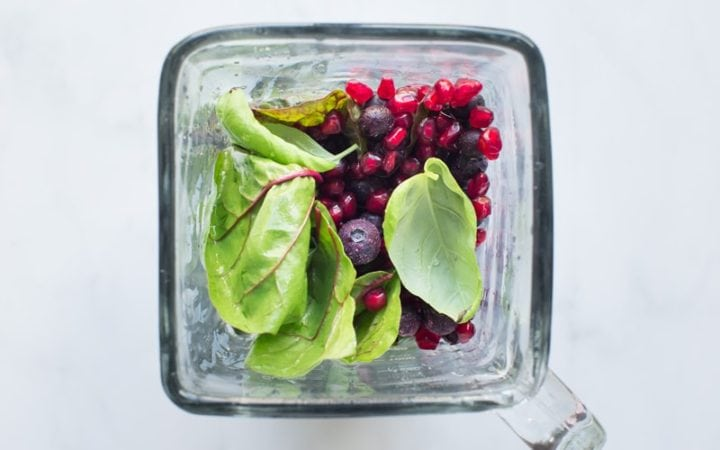 Blender filled with fruits and leafy greens to make a smoothie