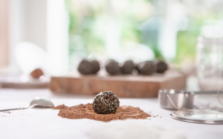 A freshly made bliss ball about to be rolled in cacao powder