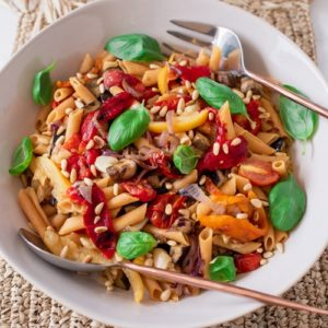 Close up of the pasta salad topped with fresh basil leaves, on a woven placement.