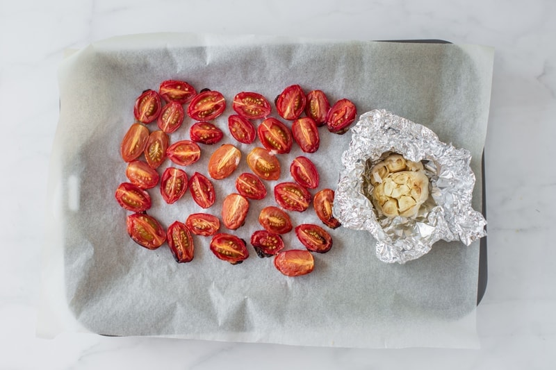 Roasting tray filed with cherry tomatoes and a head of garlic in foil