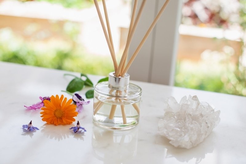 A reed diffuser by the windowsill, with a crystal beside it.