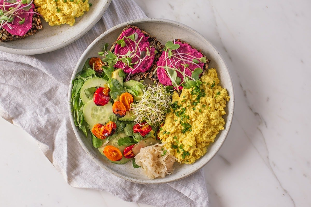 Tofu scramble on a plate with salad and seed brad