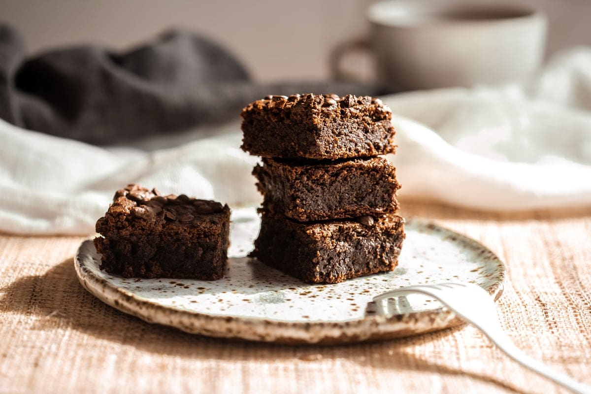 A stack of fudgy chickpea brownies on a speckled plate with a fork