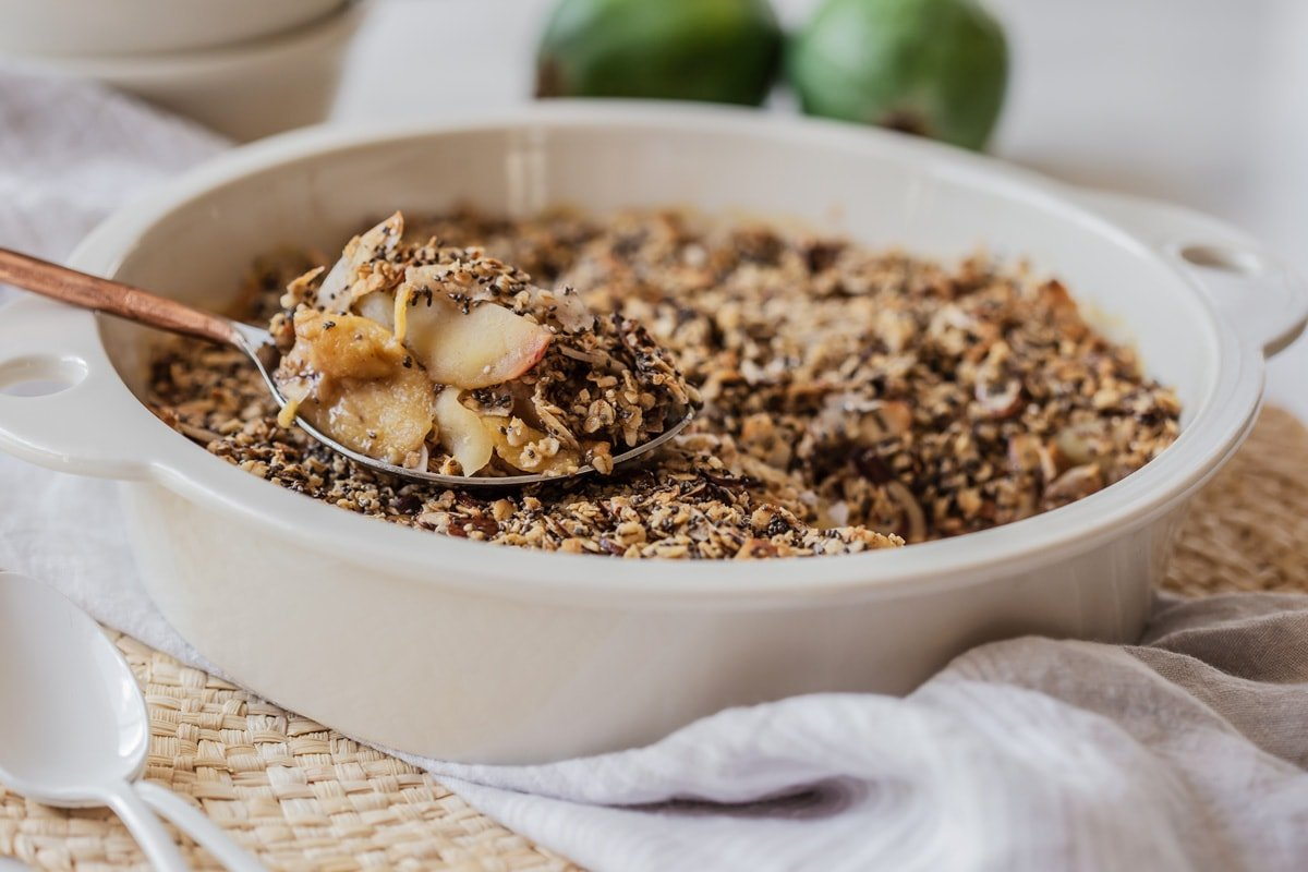 A baking dish filled with crumble, a large serving spoon on top