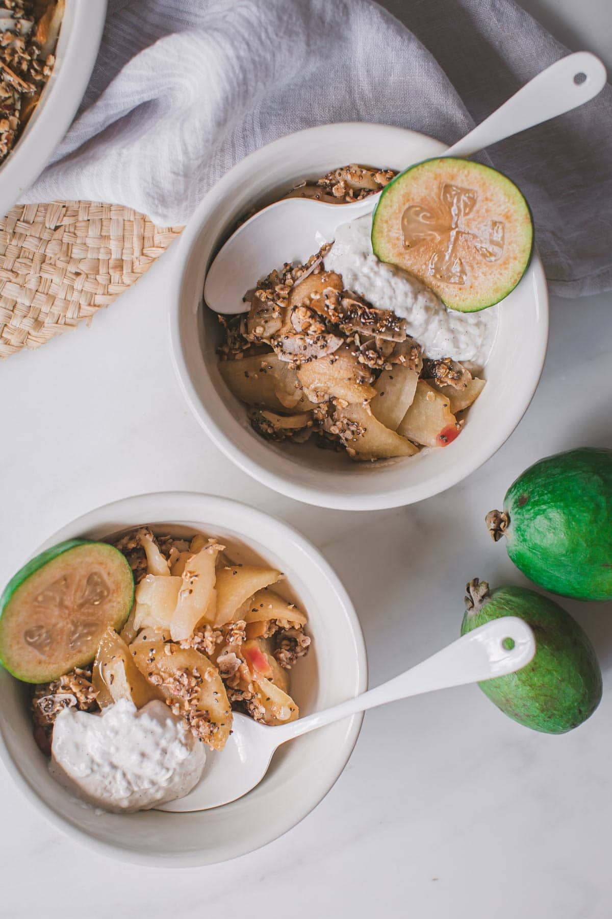 Two dessert bowls filled with feijoa crumble and a dollop of coconut yoghurt