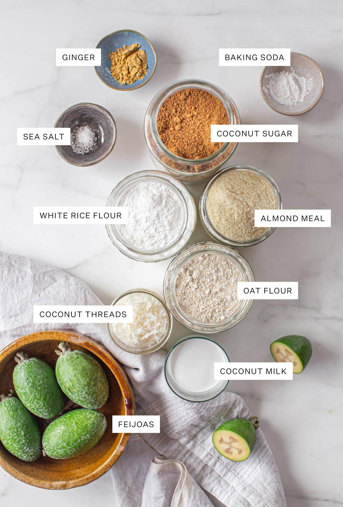 Flat lay of all the ingredients needed to make this recipe - fresh feijoas, open jars of sugar and flours, pinch bowls filled with spices, coconut milk