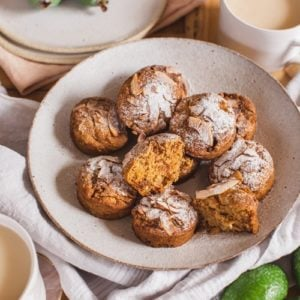 Freshly baked muffins arranged on a plate with cups of tea beside them