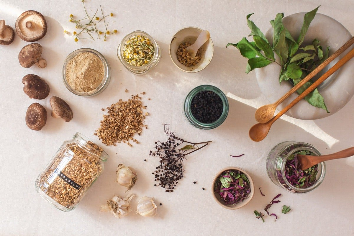 Flat lay of fresh and dried medicinal herbs over a linen tablecloth
